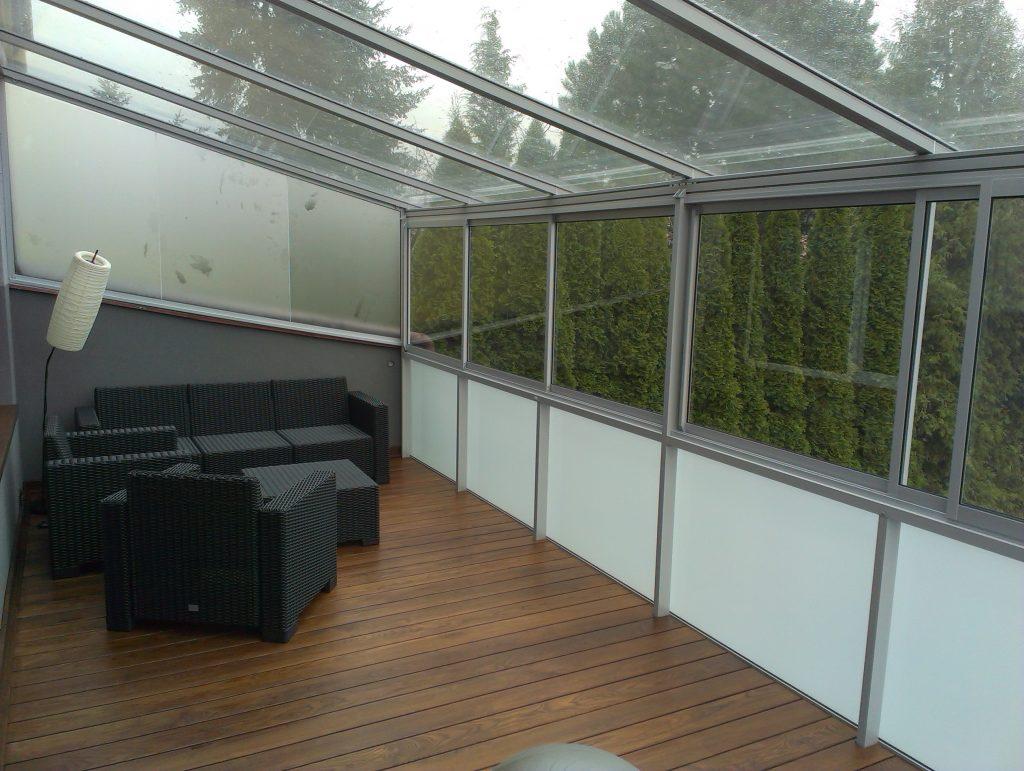 Zadaszenie tarasu z otwieranym systemem ramowym i szklaną balustradą.